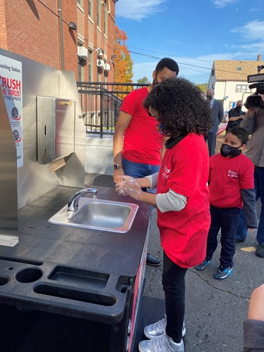 Sprague Elementary School fifth grader Lizmar Ryder demonstrates how to use Eemax's portable handwashing station.