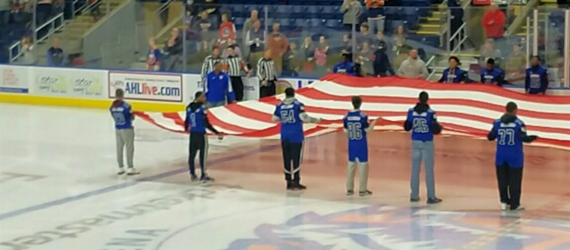 Crosby Football holding the American flag during the National Anthem at the Bridgeport Sound Tigers hockey game