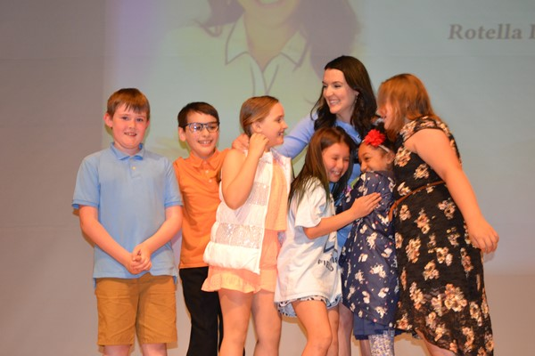 Some of Mrs. Romano's students join her onstage.